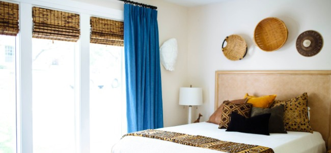 eclectic guest bedroom with woven wood shades on triple window
