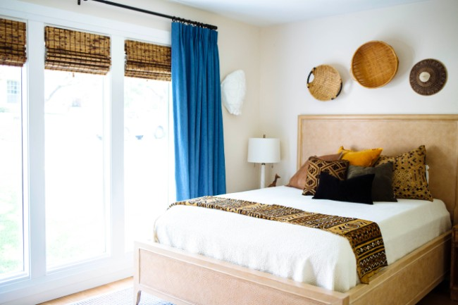 bedroom with upholstered headboard, basket wall art, African inspired textiles and woven wood shades with blue drapes