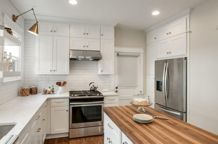 White kitchen with brass knobs and counter depth refrigerator