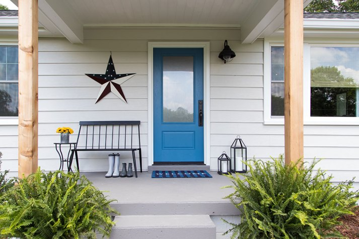 Concrete front porch with blue front door and black windsor bench