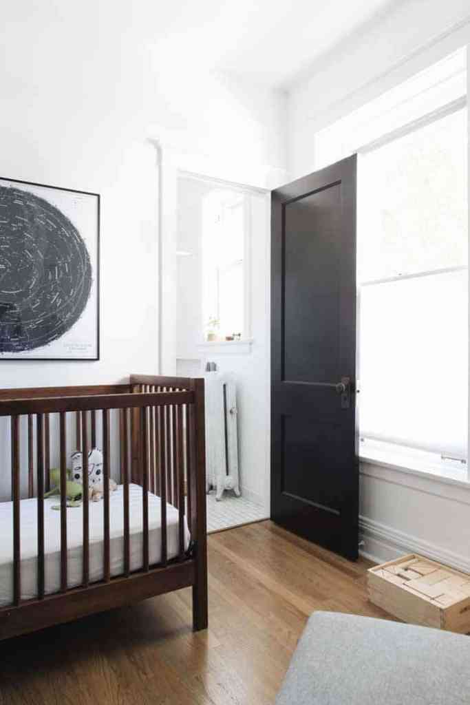 minimalist nursery with dark stained wood crib, white walls, black painted door and top down bottom up cellular shades