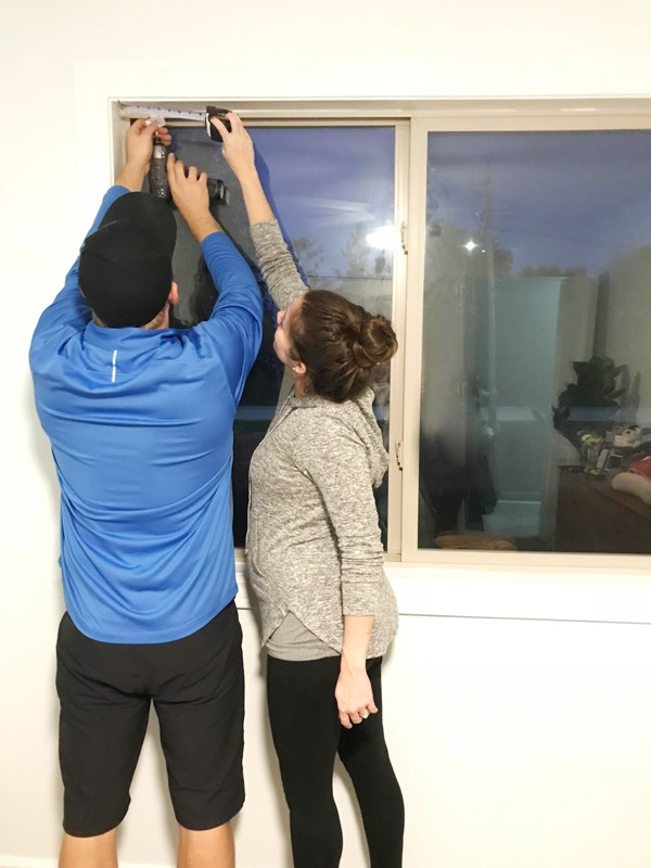 couple installing Blinds.com Roman Shades