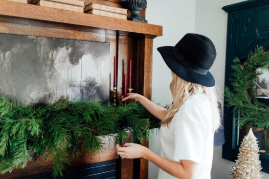 Woman with black hat decorating mantle with evergreen christmas garland