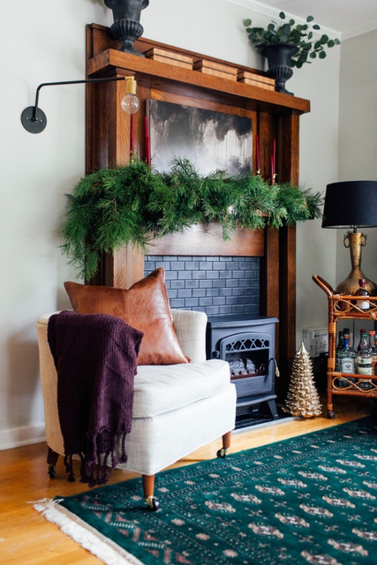 Natural Christmas decor with real evergreen garland on fireplace mantle and gold accessories
