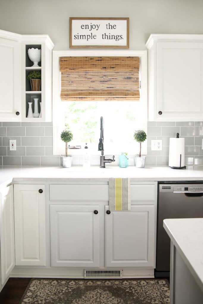 modern farmhouse kitchen with grey subway tile backsplash, white cabinets and bamboo shade on window over sink