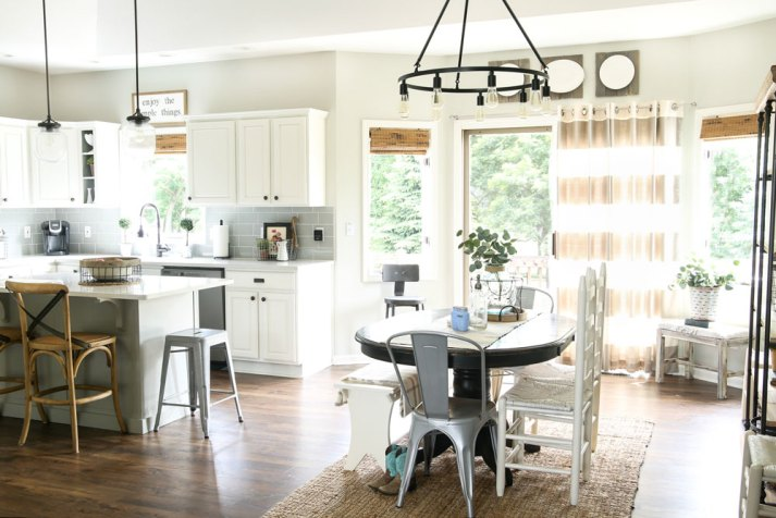 open floorplan kitchen and dining room with woven wood shades on windows