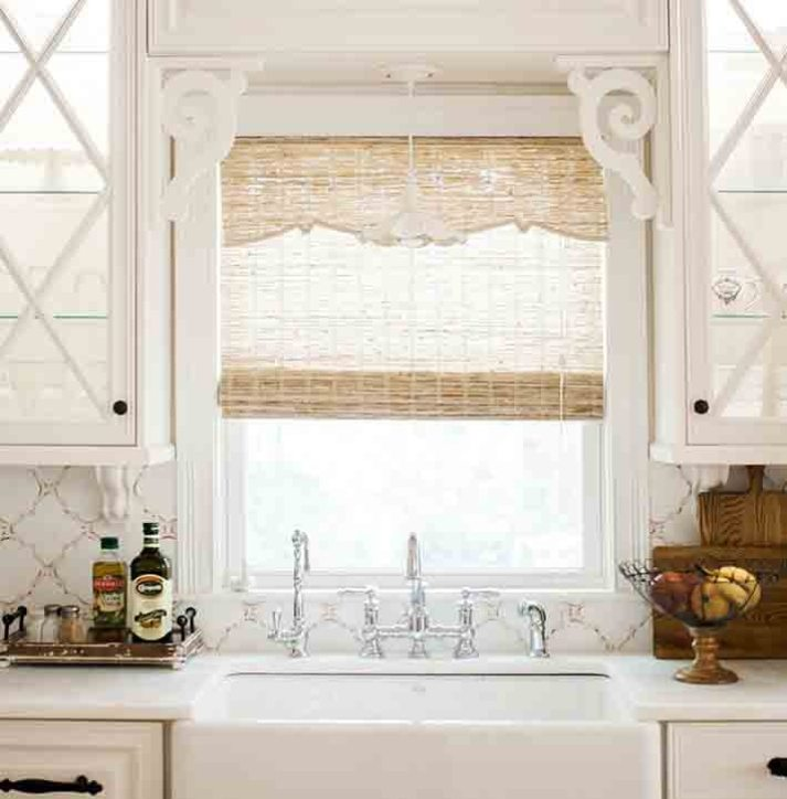 farmhouse kitchen with glass cabinet doors, trellis tile backsplash, chrome faucet and beachy woven wood shade with decorative valance