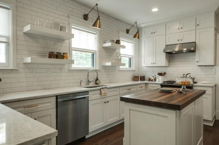 white kitchen with subway tile to ceiling, open shelving, brass swing arm lights over windows and white roller shades