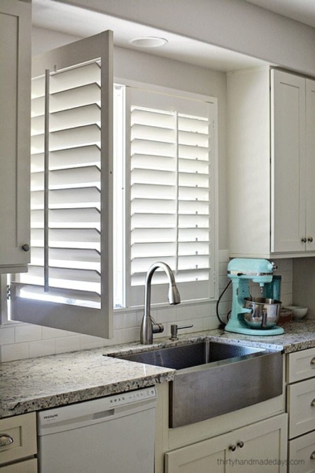 Shutters on window over kitchen sink with one panel open
