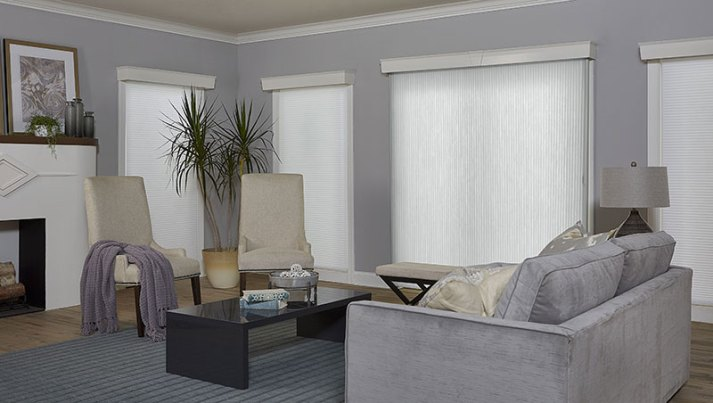grey living room with white cellular shades and sheer vertical cellular shades on sliding glass door
