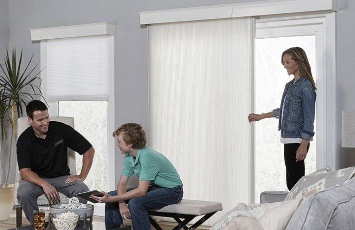 family in grey living room with vertical cellular shade for sliding patio door
