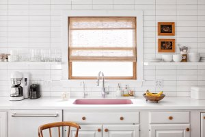 vintage inspired kitchen with pink undermount sink, white countertops, stacked subway tile backsplash to the ceiling and sheer natural window shade