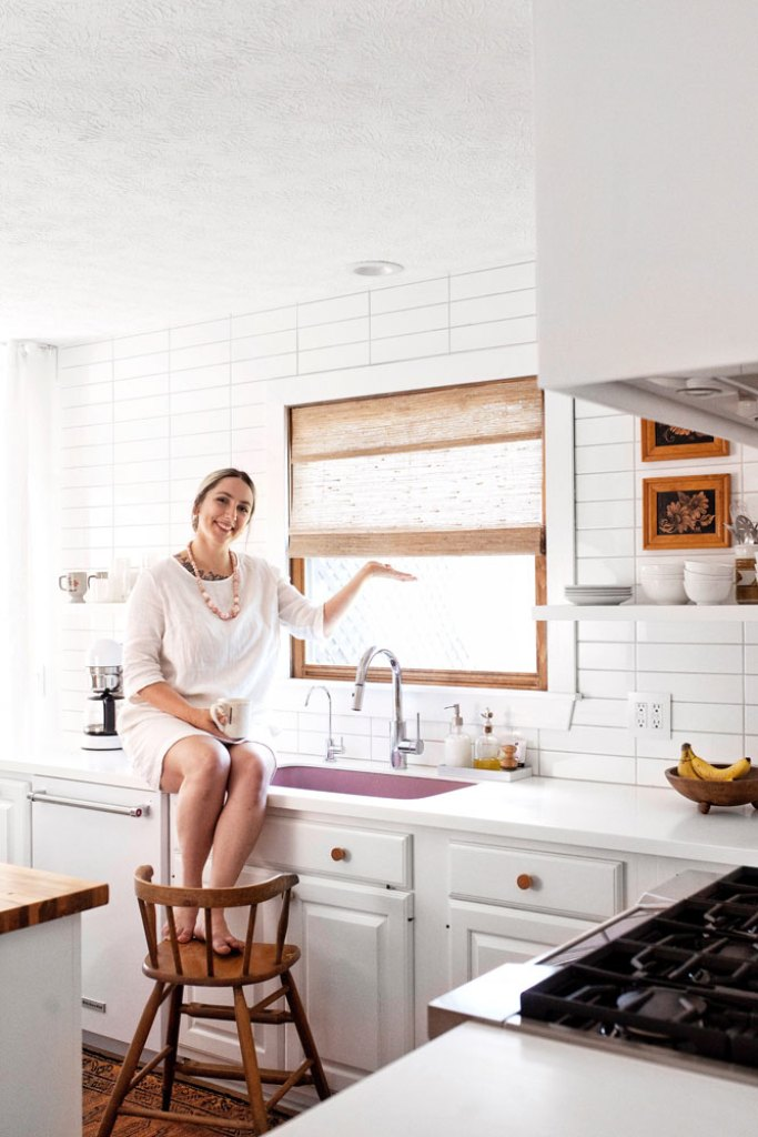 woman sitting on kitchen counter to raise cordless woven wood shade on window over sink.