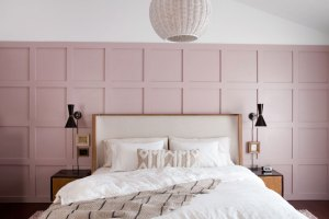 mid century bedroom with blush pink board and batten walls and oatmeal upholstered headboard
