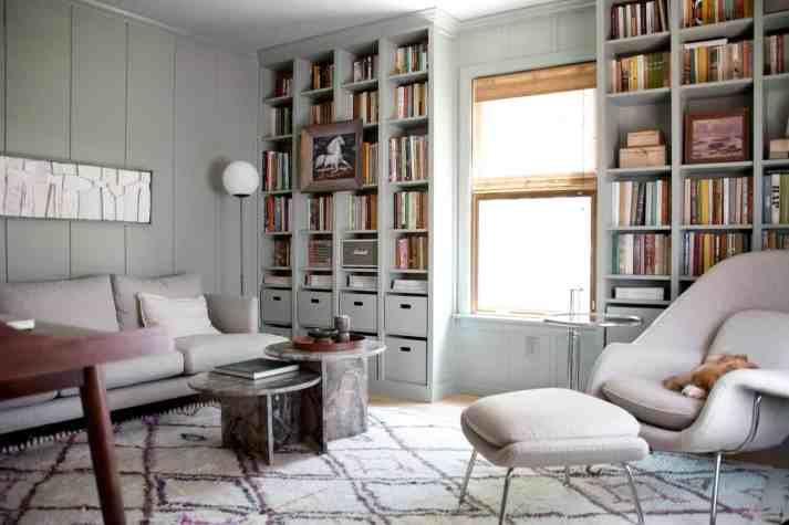vintage inspired study with seafoam built in bookcases, womb chair, grey couch and 80s stone coffee table