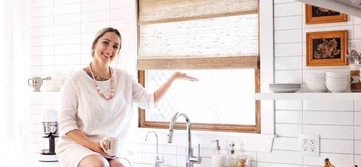 mandi johnson in renovated 70s inspired kitchen with sheer woven wood shades in window over sink