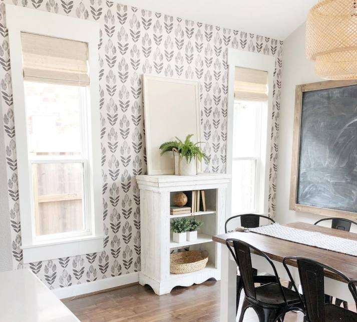 modern farmhouse dining room with printed grey and white wallpaper, wide window molding and woven grass shades in blonde color.