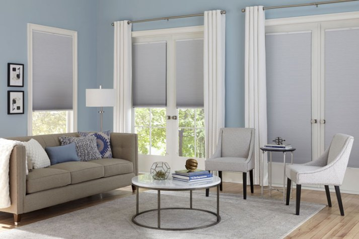 blue living room with wall of french doors covered with cellular shades and white curtains
