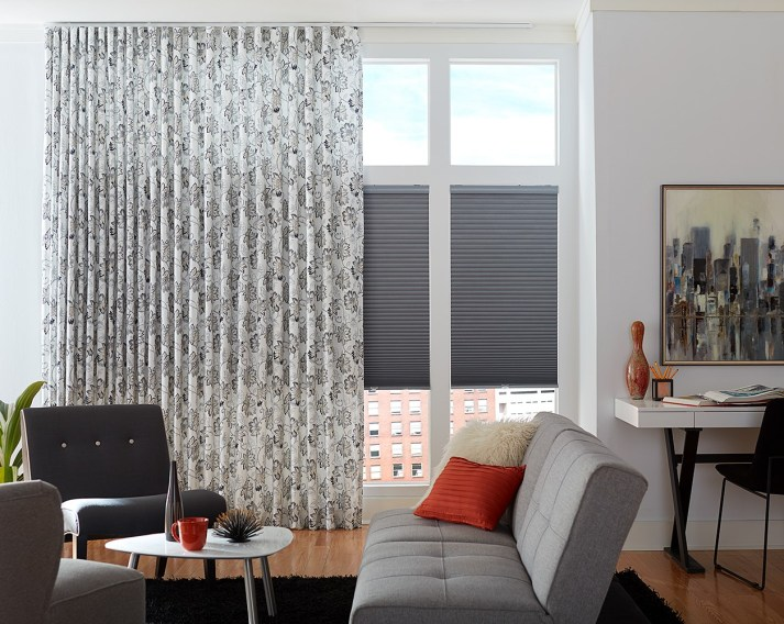 draperies hang over cellular shades in living room