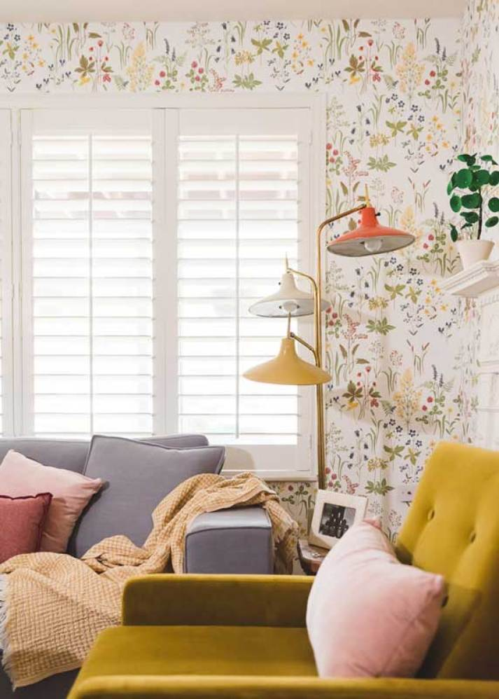 Living room corner with small print floral wallpaper in primary colors, window shutters and orange and yellow vintage lamp