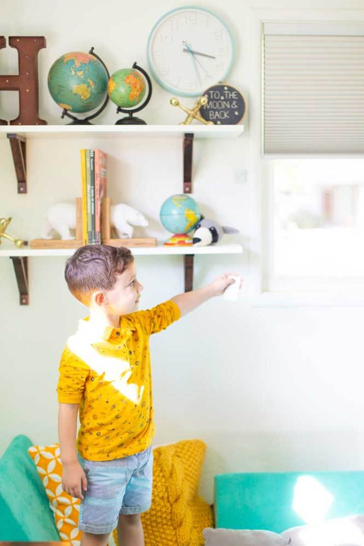 toddler boy opening motorized cellular shades with remote in eclectic bedroom