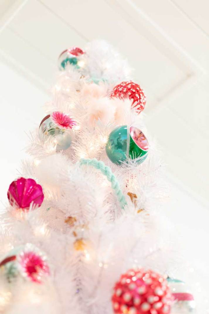 white christmas tree with colorful retro glass ornaments in green pink and red