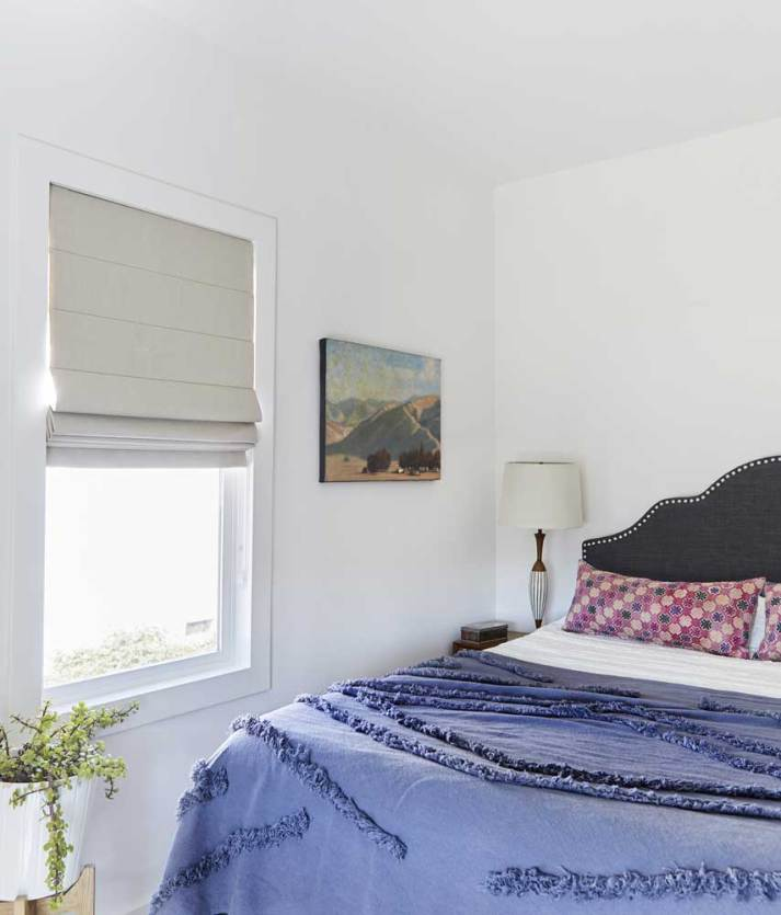 bedroom with upholstered headboard, navy tufted quilt and window with beige blackout fabric window shade