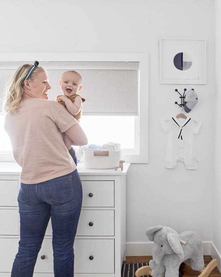 young mom holding smiling baby in nursery with blackout shade on window with small beige stripes