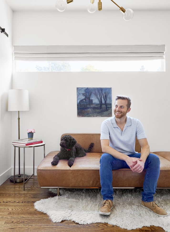 man and dog sitting on leather couch under long narrow window with grey blackout roman shade