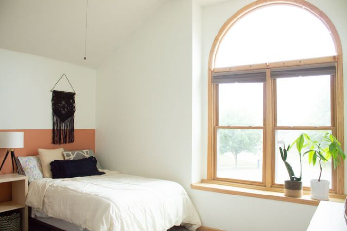 before photo of bedroom with large arched window without window treatments