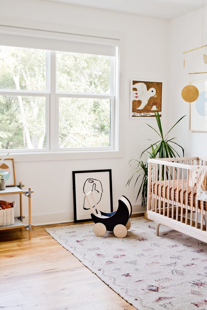 scandinavian nursery with white walls, contemporary art and blackout roller shades.