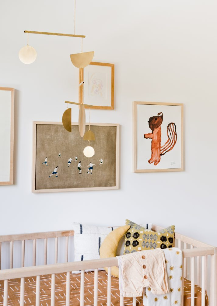 mid century nursery with unfinished wood crib, brown shibori print crib sheet, brass mobile and eclectic squirrel art.