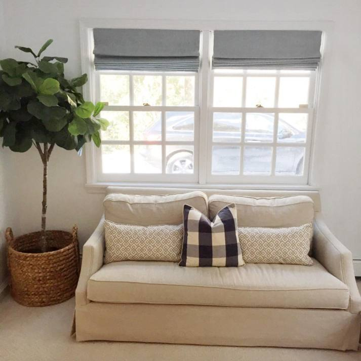 loveseat in front of window with two grey roman shades