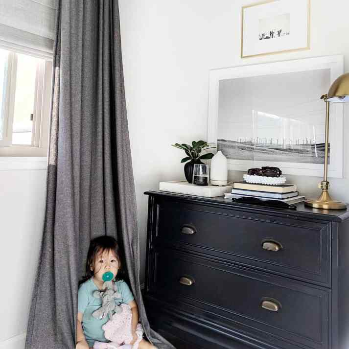toddler girl sitting on grey drapes next to black nightstand