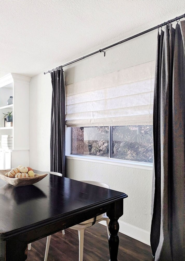 angled shot of dining room window with rustic neutral roman shades and dark grey curtains on either side