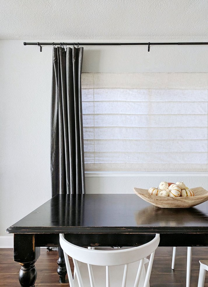 dining room with weathered black dining table, white chairs and large window with cream linen roman shades and dark grey curtains