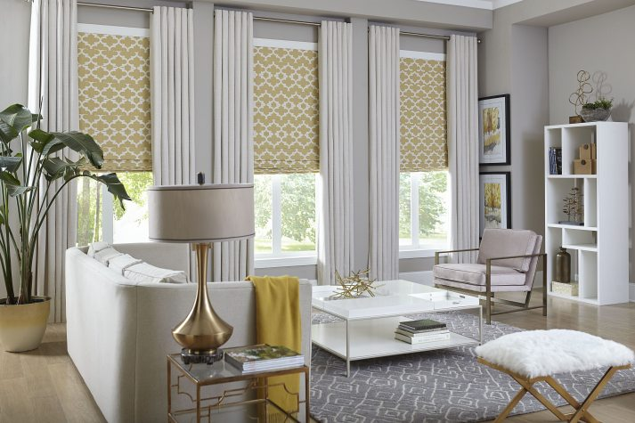 modern living room with yellow accessories, yellow patterned roman shades and cream curtains on top.