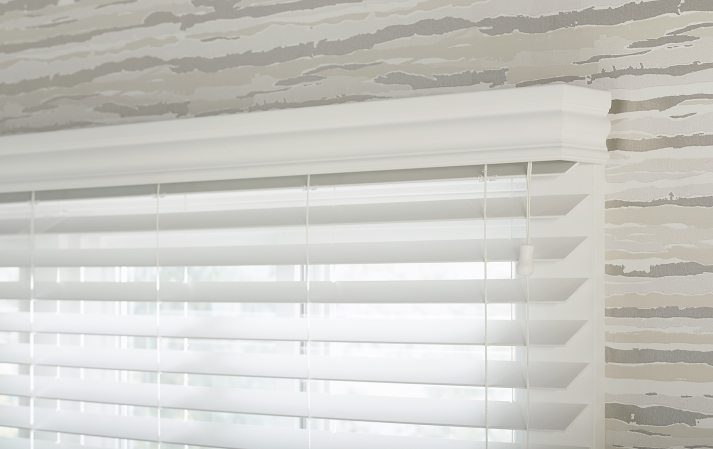 white blinds hanging over window in room with grey abstract striped wallpaper