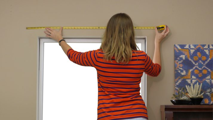 woman in red striped shirt measuring wall above window for outside mount blinds