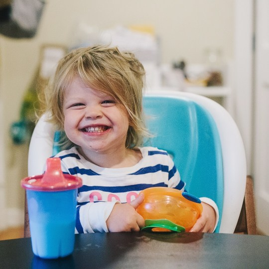 An image of my daughter at the kitchen table, grinning over her breakfast. She is in striped pajamas and has wild, messy bed-head.