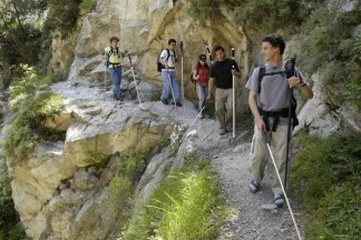 Photo of five blind hikers on a mountain trail with a slope upward on one side and a steep dropoff on the other.