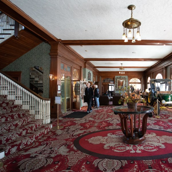 Stanley Hotel Lobby, in this image we see a Victorian decorated lobby with ornate red carpet and a large table in the center of the room.