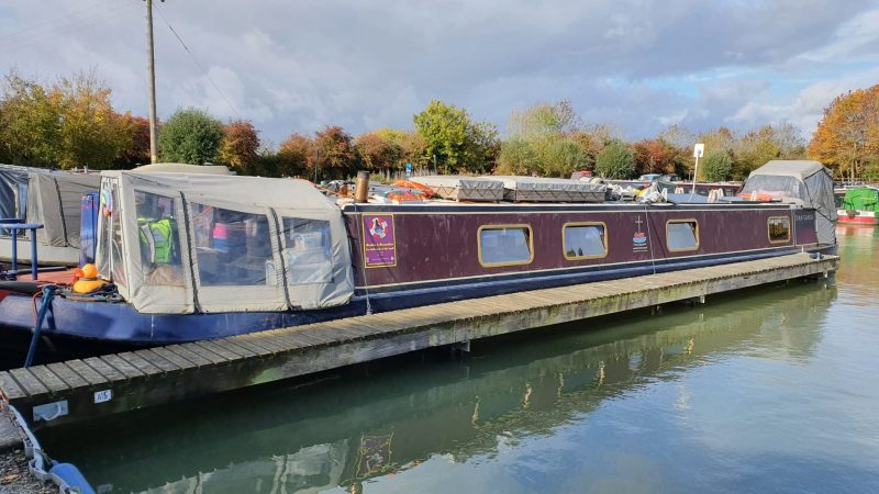 Burgundy and dark blue narrowboat with light grey canopies at front and back