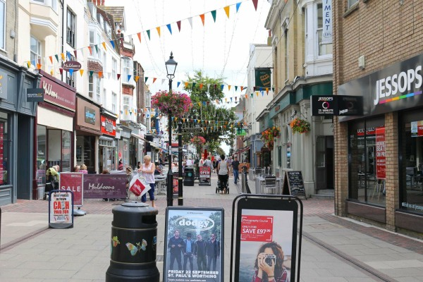 Street clutter on a pedestrianised area in Worthing. A-Boards, litter bins, street lamps and barricades around areas outside of shops create a dangerous environment for the Vision Impaired.