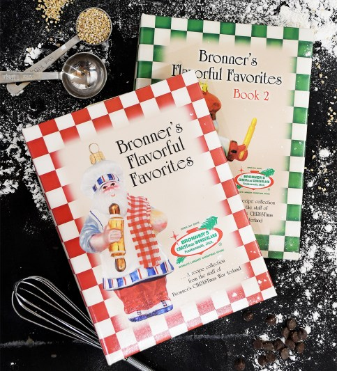 Bronner's Flavorful Favorites cookbooks, measuring spoons and a whisk lay on a black surface sprinkled with flour.
