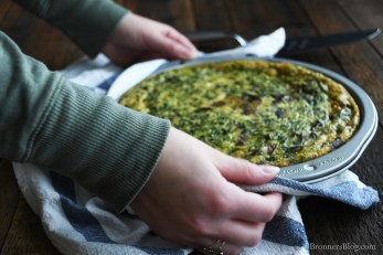 The cook is holding the summer brunch frittata with a navy and white striped towel and setting it down on a dark brown wood table top.