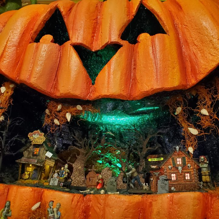 Closeup of giant jack-o'-lantern Department 56 Halloween village display featuring Dalton's Dolls, Halloween Silhouette and Haunted Huntsman House inside the wide grin of the jack-o'-lantern.