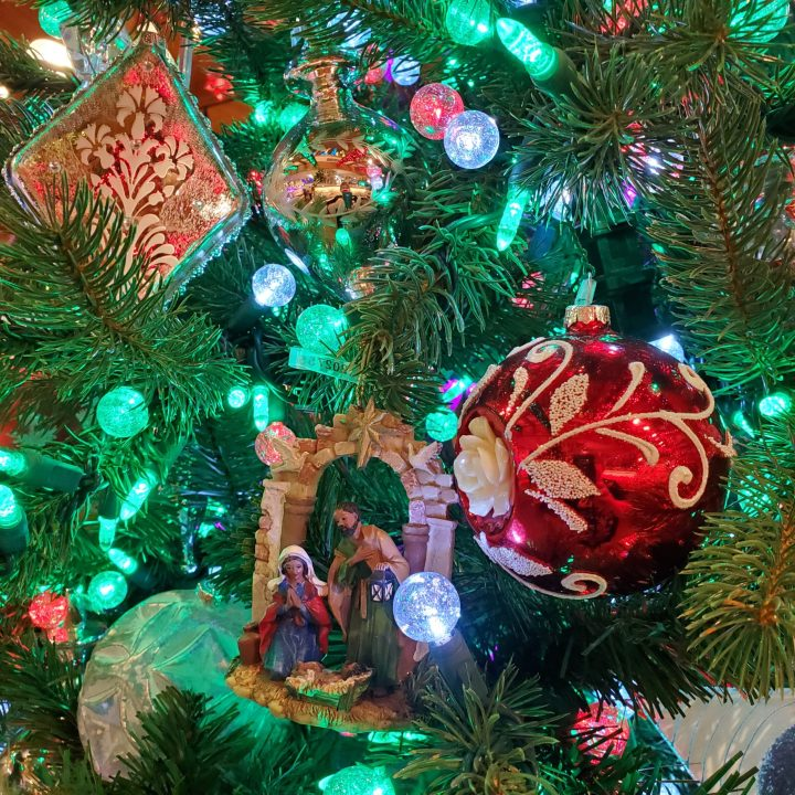 Closeup of red and white ornaments and a Holy Family ornament on a green tree with green, red and white lights