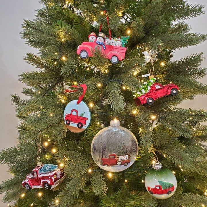 Top half of Christmas tree lit with warm white rice lights and decorated with six vintage red pickup truck ornaments.