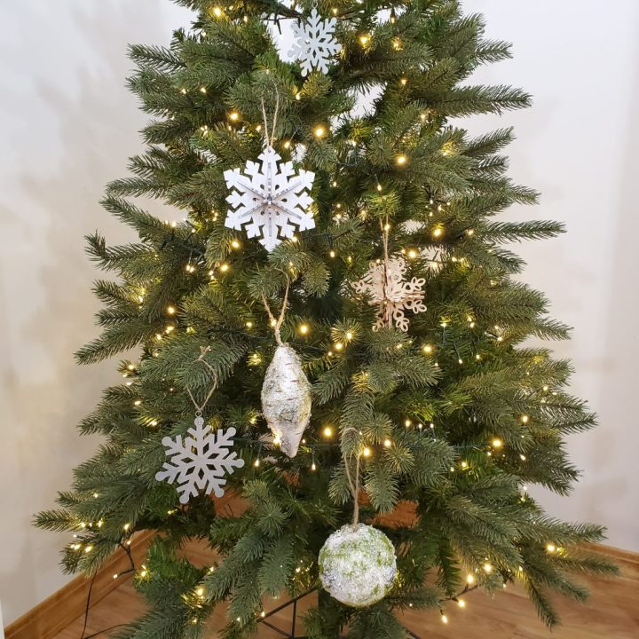 A Christmas tree lit with warm white rice lights is decorated with metal and wooden snowflakes and birch-like ornaments to reflect the natural elements trend for Christmas trends 2020.